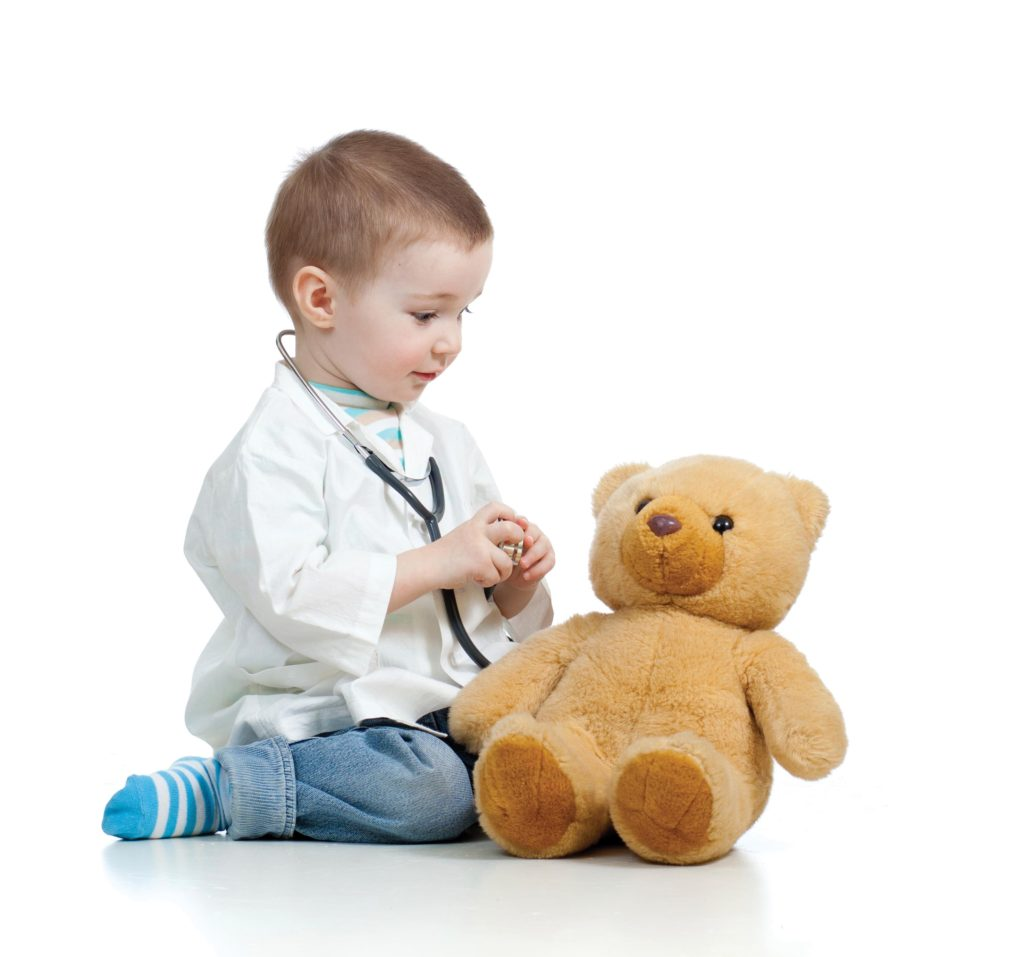 Adorable child with clothes of doctor examining teddy bear